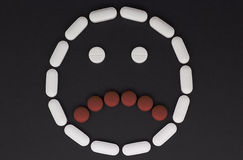 A frown face made from pills Stock Photos