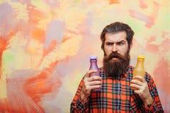 Frown gebaarde mens die twee plastic flessen houden royalty-vrije stock fotografie
