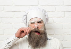 Frown man cook twirls moustache. Frown handsome man, cook or baker with flour on face and beard in chef uniform and hat twirls moustache on white brick wall Stock Image