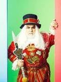 Frown senior man beefeater. Yeomen warder or male royal guard bodyguard in red uniform with spear on green wall royalty free stock image