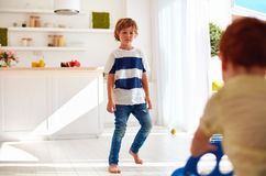 Frowned elder brother walking to junior baby at home Royalty Free Stock Photos