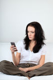Frowned young woman looks at a message on her cell phone Stock Photo