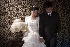 Frowning asian couple. Frowning newly wed asian couple Royalty Free Stock Images