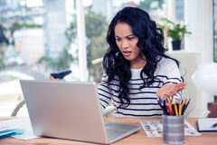 Frowning Asian woman looking at laptop Royalty Free Stock Image