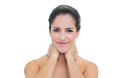 Frowning bare brunette touching her neck with both hands Royalty Free Stock Photography