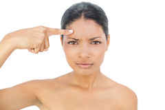 Frowning black haired model pointing at her forehead Stock Photo