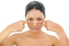 Frowning black haired model pressing blackhead on her nose Stock Images