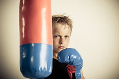 Frowning blond boy stands beside punching bag. Frowning blond boy with boxing gloves stands beside blue and red punching bag in a room with low lighting Stock Photos