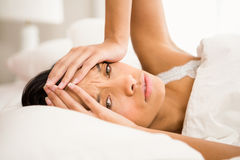 Frowning brunette in bed. With hands on face royalty free stock photo