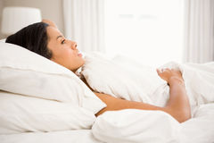 Frowning brunette in bed. At home royalty free stock photo