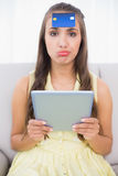 Frowning brunette with credit card on forehead holding tablet Royalty Free Stock Photo