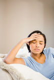 Frowning brunette with hand on face. On the sofa Royalty Free Stock Images
