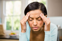 Frowning brunette with headache. In the kitchen Stock Images