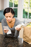 Frowning brunette holding receipt and milk. In the kitchen Royalty Free Stock Images
