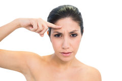 Frowning brunette pointing to forehead and looking at camera Stock Photos