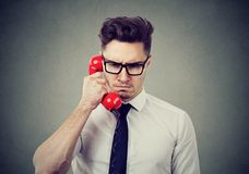 Frowning business man having unpleasant telephone conversation. Serious frowning young business man having unpleasant telephone conversation unhappy with bad Stock Photos