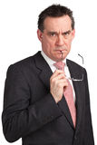 Frowning Business Man in Suit Holding Glasses Royalty Free Stock Photography