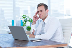 Frowning businessman looking at his laptop Stock Images