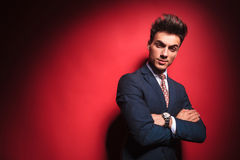 Frowning businessman with red tie and hands crossed. Portrait of confident young businessman in black suit with red tie posing with hands crossed while frowning Stock Image