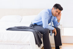 Frowning businessman sitting at edge of bed Stock Images