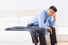 Frowning businessman sitting at edge of bed looking at camera Stock Photo
