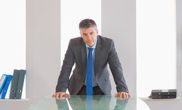 Frowning businessman standing in front of a desk Royalty Free Stock Photography