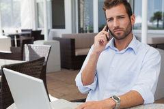 Frowning businessman talking on phone using his laptop. In patio of restaurant Stock Photos