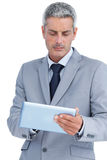 Frowning businessman using digital tablet Stock Photos
