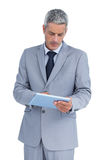 Frowning businessman using tablet pc Stock Photos