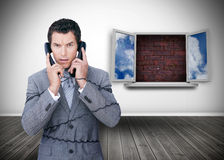 Frowning businessman wrapped in cables phoning Royalty Free Stock Image