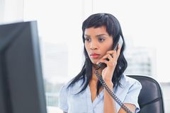 Frowning businesswoman answering the telephone Stock Images