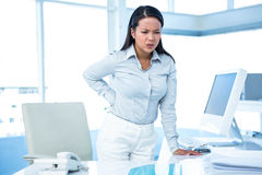 Frowning businesswoman with back ache Royalty Free Stock Images