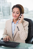 Frowning businesswoman phoning Royalty Free Stock Photography