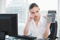 Frowning businesswoman showing calculator sitting at desk Royalty Free Stock Photo