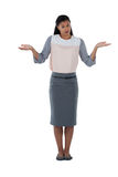 Frowning businesswoman shrugging her shoulders. Against white background Stock Photography