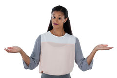 Frowning businesswoman shrugging her shoulders. Against white background Stock Image