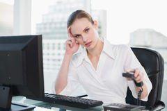 Frowning businesswoman sitting at desk hanging up phone Royalty Free Stock Photos