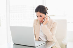 Frowning businesswoman working with a laptop on the phone Royalty Free Stock Photos