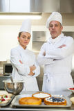 Frowning chef and head chef standing arms crossed. In professional kitchen stock image