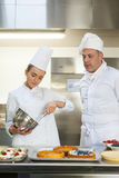 Frowning chef whisking while being watched by head chef Stock Image