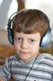 Frowning child. In headphones Royalty Free Stock Photo