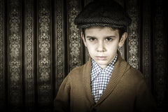 Frowning child in vintage clothes and hat Stock Images