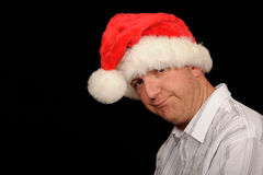 Frowning Christmas Man. A metaphorical image of a man wearing a Christmas cap frowning with sadness, on a black studio background Royalty Free Stock Image