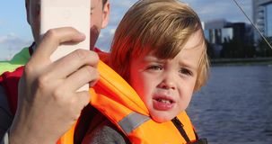 Upset boy with father riding in boat stock video footage