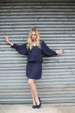 Frowning elegant blonde wearing classy dress posing outdoors Royalty Free Stock Image