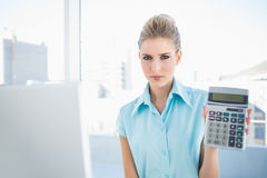 Frowning elegant woman showing calculator Royalty Free Stock Photos