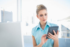 Frowning elegant woman using calculator Royalty Free Stock Photo