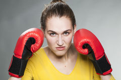 Frowning female boxer fists up and hair tied back Royalty Free Stock Photography