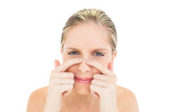 Frowning fresh blonde woman pressing her nose Stock Photo
