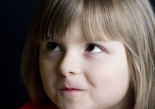 Frowning girl. Portrait of frowning young girl, black background Royalty Free Stock Images
